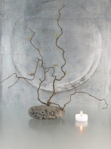 Gesteck mit Zweigen und Kerze